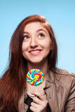 Szczęśliwa młoda dziewczyna z lizakiem na błękicie Zdjęcia Royalty Free