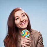 Szczęśliwa młoda dziewczyna z lizakiem na błękitnym tle Zdjęcia Stock