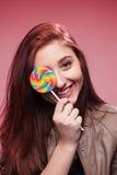 Szczęśliwa młoda dziewczyna z lizakiem na menchii Fotografia Royalty Free