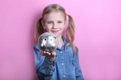 Szczęśliwa młoda dziewczyna z srebnym prosiątko bankiem na różowym tle koncepcja pieniędzy, żeby ratować obraz royalty free