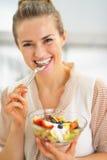 Szczęśliwa młoda gospodyni domowa je świeżej owocowej sałatki Obraz Stock