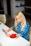 Szczęśliwa młoda gospodyni domowa je owoc z pastylka komputerem osobistym Zdjęcia Stock