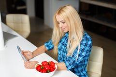 Szczęśliwa młoda gospodyni domowa je owoc z pastylka komputerem osobistym Fotografia Royalty Free