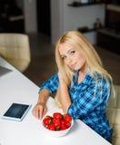 Szczęśliwa młoda gospodyni domowa je owoc z pastylka komputerem osobistym Obrazy Royalty Free