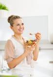 Szczęśliwa młoda gospodyni domowej łasowania owoc sałatka Fotografia Stock