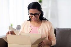 Szczęśliwa młoda indyjska kobieta z pakuneczka pudełkiem w domu zdjęcia royalty free