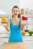 Szczęśliwa młoda kobieta żongluje z dzwonkowymi pieprzami Obrazy Royalty Free