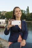 Szczęśliwa młoda kobieta bierze obrazki z mądrze telefonem Zdjęcia Royalty Free