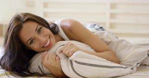 Szczęśliwa młoda kobieta cuddling up w łóżku zdjęcie wideo