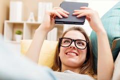 Szczęśliwa młoda kobieta czyta ebook na jej leżance Fotografia Stock