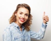 Szczęśliwa młoda kobieta daje kciukowi up zdjęcie stock
