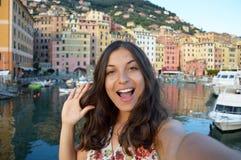 Szczęśliwa młoda kobieta garbnikował brać selfie fotografię w typowym włocha krajobrazie z schronieniem i kolorowymi domami dla w Zdjęcia Stock
