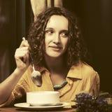 Szczęśliwa młoda kobieta je polewkę przy restauracją zdjęcie stock