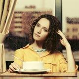 Szczęśliwa młoda kobieta je polewkę przy restauracją w żółtej koszula fotografia royalty free