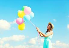 Szczęśliwa młoda kobieta jest ubranym lato słomianego kapelusz nad niebieskiego nieba tłem z lotniczy kolorowi balony ma zabawę fotografia royalty free