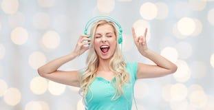 Szczęśliwa młoda kobieta lub nastoletnia dziewczyna z hełmofonami Obrazy Royalty Free
