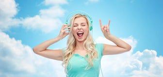 Szczęśliwa młoda kobieta lub nastoletnia dziewczyna z hełmofonami Obraz Stock