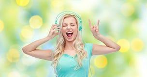 Szczęśliwa młoda kobieta lub nastoletnia dziewczyna z hełmofonami Fotografia Royalty Free