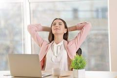 Szczęśliwa młoda kobieta ma krótkiego odpoczynek przy miejscem pracy obrazy royalty free