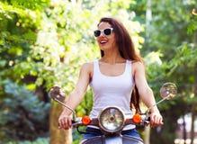 Szczęśliwa młoda kobieta na hulajnoga w miasto parku w lecie obraz royalty free