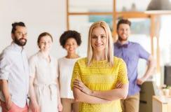 Szczęśliwa młoda kobieta nad kreatywnie drużyną w biurze Fotografia Royalty Free