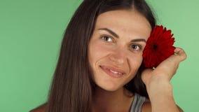 Szczęśliwa młoda kobieta ono uśmiecha się, stawiający kwiatu w jej włosy zbiory wideo