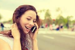 Szczęśliwa młoda kobieta opowiada na telefonu komórkowego odprowadzeniu na ulicie Zdjęcie Royalty Free