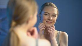 Szczęśliwa młoda kobieta patrzeje lustrzanego odbicie, satysfakcjonującego z skóry traktowaniem zbiory