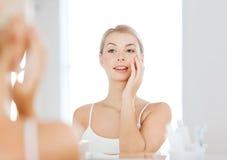 Szczęśliwa młoda kobieta patrzeje odzwierciedlać przy łazienką Zdjęcie Stock