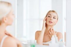 Szczęśliwa młoda kobieta patrzeje odzwierciedlać przy łazienką Obraz Royalty Free