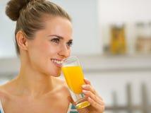 Szczęśliwa młoda kobieta pije świeżego sok pomarańczowego Obrazy Royalty Free