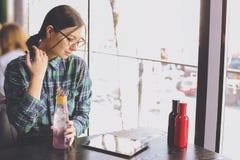 Szczęśliwa młoda kobieta pije cappuccino, używa pastylka komputer i opowiada na telefonie w, latte, macchiato, herbata, sklep z k Fotografia Stock
