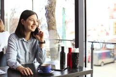 Szczęśliwa młoda kobieta pije cappuccino, używa pastylka komputer i opowiada na telefonie w, latte, macchiato, herbata, sklep z k zdjęcia stock