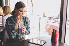 Szczęśliwa młoda kobieta pije cappuccino, używa pastylka komputer i opowiada na telefonie w, latte, macchiato, herbata, sklep z k Obraz Stock
