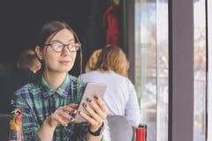 Szczęśliwa młoda kobieta pije cappuccino, używa pastylka komputer i opowiada na telefonie w, latte, macchiato, herbata, sklep z k Obraz Royalty Free