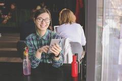 Szczęśliwa młoda kobieta pije cappuccino, używa pastylka komputer i opowiada na telefonie w, latte, macchiato, herbata, sklep z k Fotografia Royalty Free