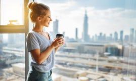 Szczęśliwa młoda kobieta pije kawę w ranku przy okno Fotografia Royalty Free