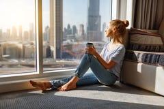 Szczęśliwa młoda kobieta pije kawę w ranku przy okno Obraz Royalty Free