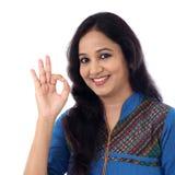 Szczęśliwa młoda kobieta pokazuje OK gest przeciw bielowi fotografia royalty free