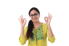 Szczęśliwa młoda kobieta pokazuje OK gest przeciw bielowi zdjęcie stock