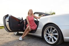Szczęśliwa młoda kobieta pozuje w odwracalnym samochodzie obrazy stock