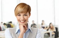 Szczęśliwa młoda kobieta przy biurem Obrazy Royalty Free