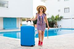 Szczęśliwa młoda kobieta przyjeżdża kurort z błękitnym bagażem Chodzi obok pływackiego basenu Zaczynać Zdjęcie Royalty Free