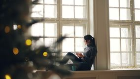 Szczęśliwa młoda kobieta relaksuje w domu i cieszy się nowożytny używa smartphone obsiadanie na windowsill na święto bożęgo narod zbiory wideo