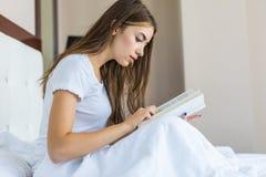 Szczęśliwa młoda kobieta relaksuje w domu i czyta książkę zdjęcia stock