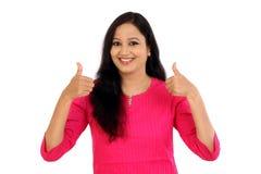 Szczęśliwa młoda kobieta robi aprobata gestowi przeciw bielowi Obraz Royalty Free