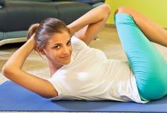 Szczęśliwa młoda kobieta robi sprawności fizycznej w domu. obrazy royalty free