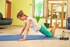 Szczęśliwa młoda kobieta robi sprawności fizycznej w domu. obraz stock