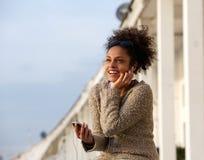Szczęśliwa młoda kobieta słucha muzyka na telefonie komórkowym Obrazy Royalty Free
