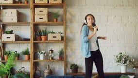 Szczęśliwa młoda kobieta słucha muzyka w hełmofonach, tanczący na kanapie i śpiewie w hairbrush w jak mikrofon, dziewczyna zbiory wideo